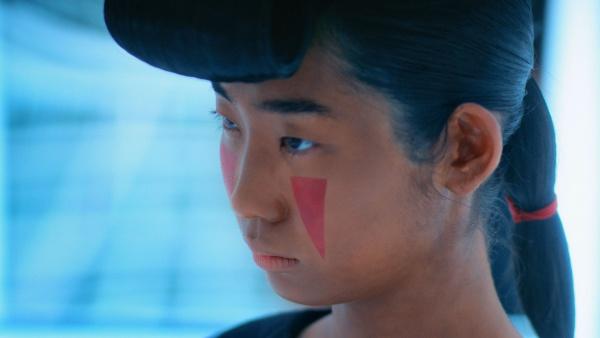 目の下の赤い逆三角形の化粧がポイント。
