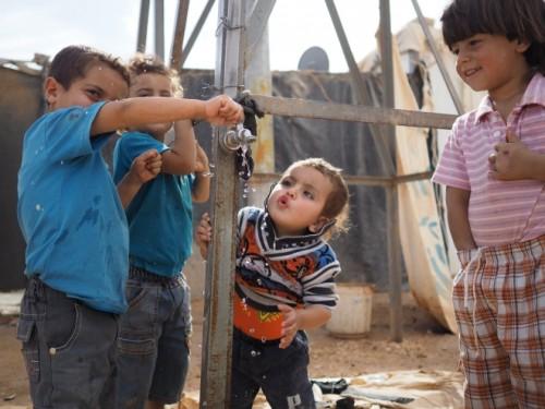 ヨルダン北部に位置する、ザータリ難民キャンプ。壊れかけた水タンクの周りに、子どもたちが集う。