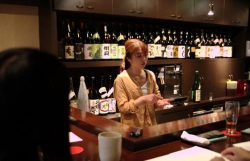 「焼酎楽味隠れが『陽』」の女将・仮谷陽さん(奥)と熱心にメモを取る参加者。