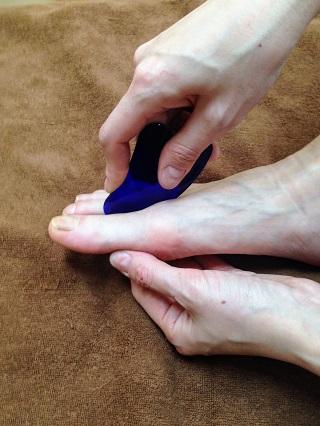 かっさを使って足のおや指のつけ根を指圧する。
