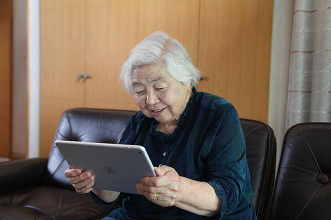 タブレットでツイッターや離れて暮らす家族とのコミュニケーションを楽しむミゾイキクコさん