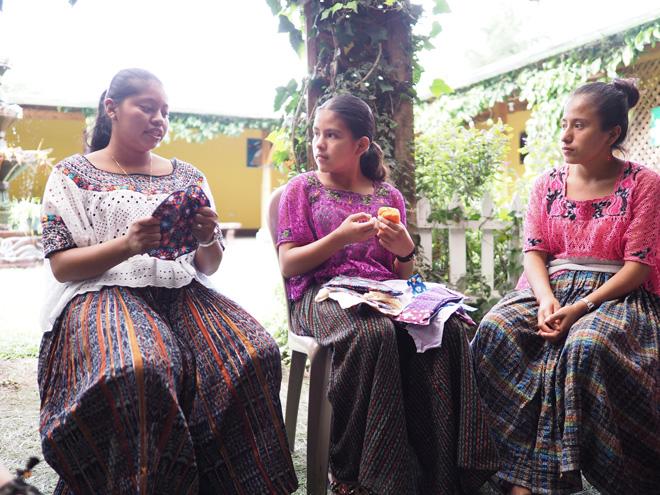 生理についてや、女性が置かれた状況について、同じコミュニティー出身の少女たちと語るエベリンさん(左)。