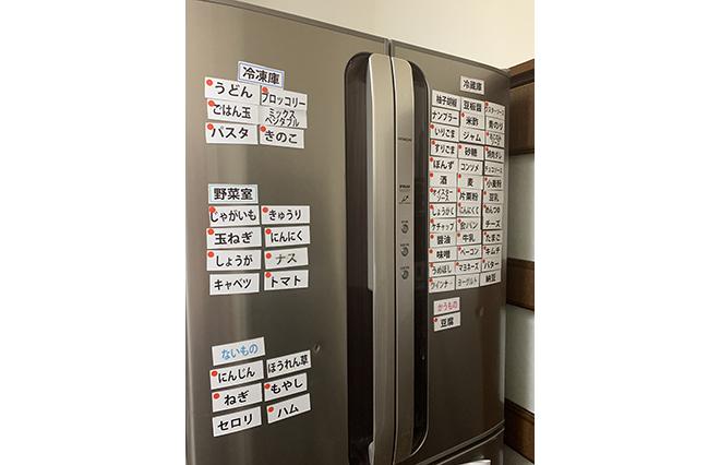 一目で冷蔵庫・冷凍庫にあるものがわかるマグネットシート。共同で使う食材にはオレンジ色の丸いシールが貼られている。