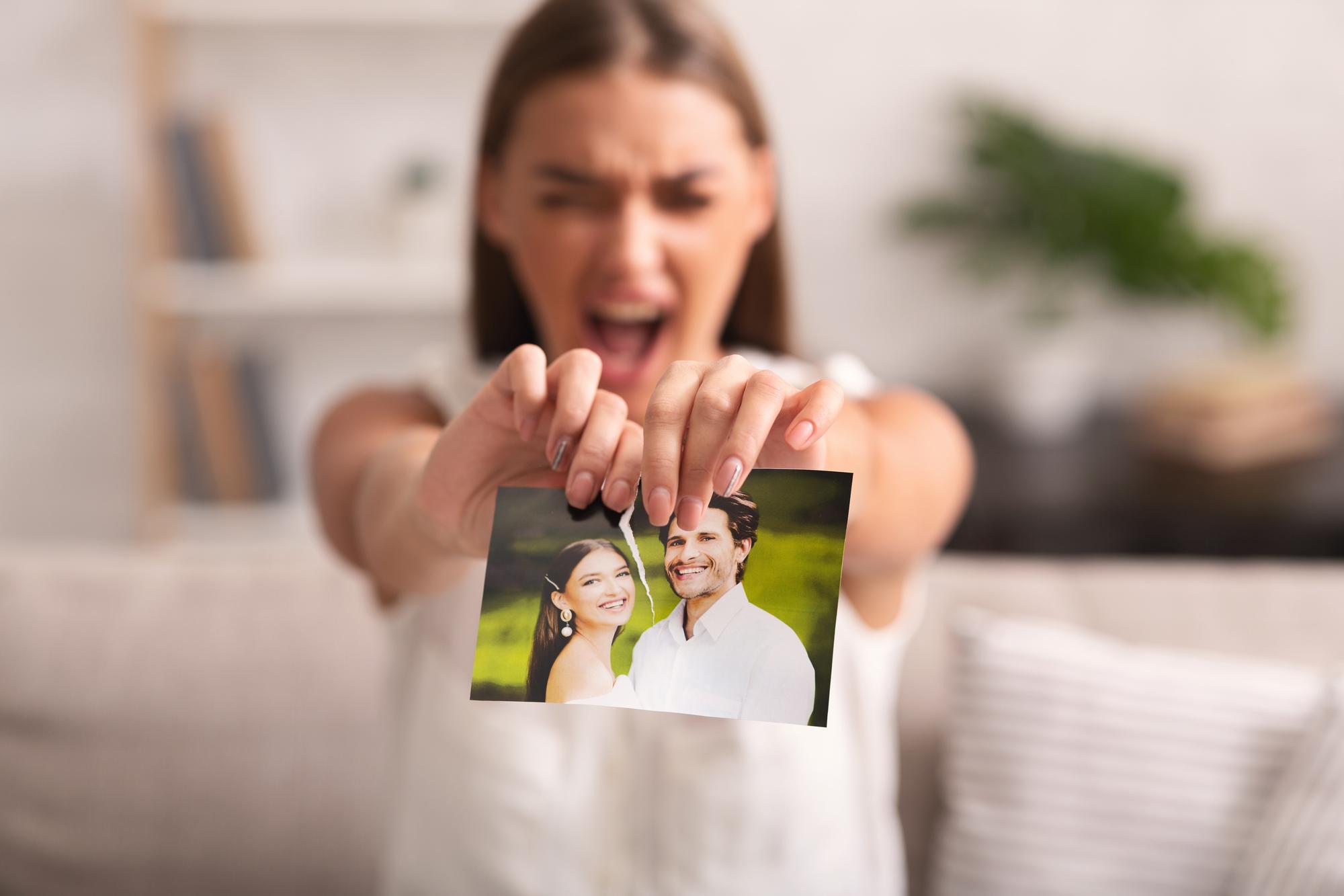 Furious Woman Ripping Wedding Photo Sitting On Sofa Indoor
